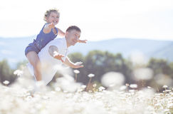 Father and daughter in summer field of blooming daisies Royalty Free Stock Photo