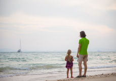 Father and daughter on sunset ocean beach and yacht on back Stock Photo