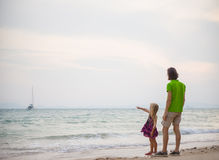 Father and daughter on sunset ocean beach and yacht on back Stock Photography