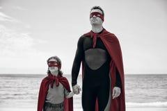 Father and daughter in superhero costume sea shore Stock Image