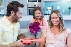 Father and daughter surprising mother with gift. At home in the living room Stock Images