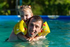 Father and daughter swim in pool. Girl riding on man. She swims in pillows. Royalty Free Stock Photo