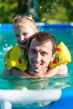 Father and daughter swim in pool. Girl riding on man. She swims in pillows. Stock Photos