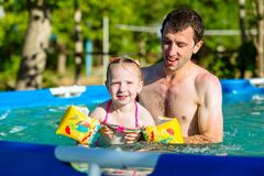 Father and daughter swim in pool. Girl swims in pillows. Royalty Free Stock Image