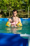 Father and daughter swim in pool. Girl swims in pillows. Stock Image