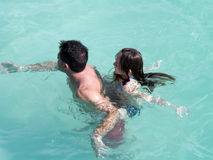 Father and daughter swimming. High angle view of father and daughter swimming in water Royalty Free Stock Image