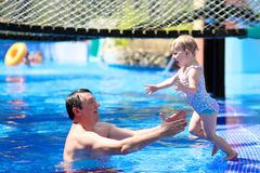 Father and daughter swimming in outdoors pool Stock Photography