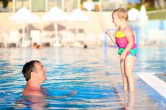 Father and daughter swimming in outdoors pool Royalty Free Stock Photography