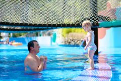 Father and daughter swimming in outdoors pool Stock Image