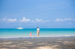 Father and daughter in swimming suit play on ocean beach with ya Royalty Free Stock Images