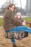 Father and daughter swinging Royalty Free Stock Photos