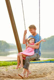 Father and daughter swinging together Royalty Free Stock Photography