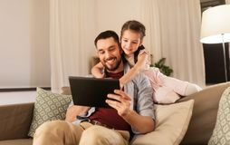 Father and daughter with tablet computer at home royalty free stock photo