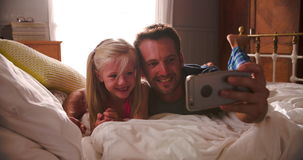 Father And Daughter Take Selfie On Mobile Phone Lying On Bed. Father and daughter lie on bed together and take selfie on mobile phone.Shot on Sony FS700 at frame stock footage