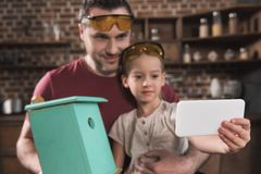 Father and daughter taking selfie with self-made birdhouse with smartphone stock photo