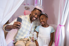 Father and daughter taking selfie while sitting on bed at home Stock Images