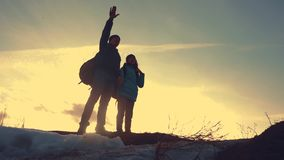 Father and daughter teamwork happy family tourists silhouette concept navigation . team dad and daughter on top of a. Mountain at sunset raise shows direction stock video