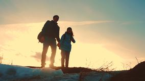 Father and daughter teamwork happy family tourists silhouette concept navigation . team dad and daughter on top of a. Mountain at sunset raise shows the stock video footage