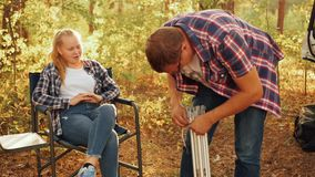 Father and daughter teenager on family picnic in autumn forest. Man preparing table for preparing food at autumn picnic. In countryside forest stock footage
