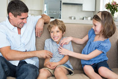 Father and daughter tickling boy on sofa stock photo