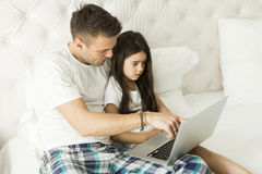 Father and daughter. Together on the bed with a laptop royalty free stock image