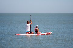 Father and daughter together paddling on a sup board.  royalty free stock image