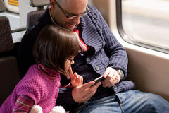 Father and daughter on train with smart phone Stock Photography