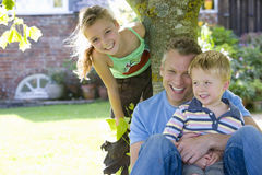 Father and daughter (7-9) by tree, son (2-4) on lap, smiling, portrait stock photography