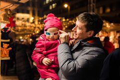 Father and daughter try on 3D glasses on Christmas Market at they St. Stephen`s Square in front of the St. Stephen`s Basilica. royalty free stock photos