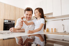 Father and daughter trying to match jigsaw puzzle pieces Royalty Free Stock Photography