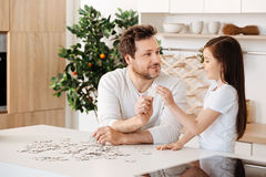 Father and daughter uniting two jigsaw puzzle pieces Stock Photo
