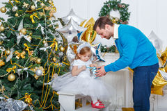 Father and daughter unpacked gifts at the Christmas tree. Stock Image