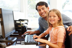 Father and daughter using computer in home office Stock Photography