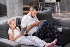 Father and daughter using digital devices. Father and daughter sitting on grey sofa and using digital devices Royalty Free Stock Photography