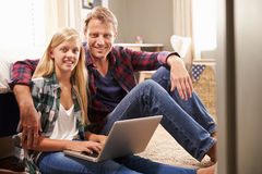 Father and daughter using laptop computer together at home Royalty Free Stock Images