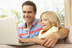 Father And Daughter Using Laptop At Home Stock Photo