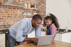 Father And Daughter Using Laptop In Kitchen At Home Stock Photography