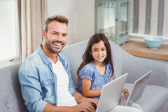 Father and daughter using laptop while sitting on sofa Stock Photo