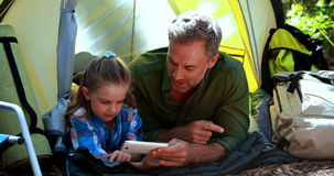 Father and daughter using mobile phone outside tent. At campsite stock footage