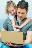 Father and daughter using notebook. Stock Photo