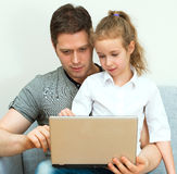 Father and daughter using notebook. Stock Photography