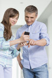 Father and daughter using smart phone at home Royalty Free Stock Photo