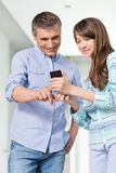 Father and daughter using smart phone at home Stock Images