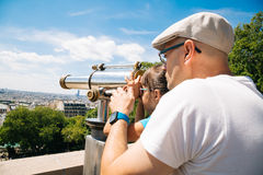 Father and daughter using a telescope in Paris Stock Photo