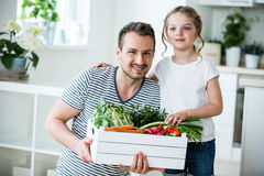 Father and daughter with vegetable box in kitchen Royalty Free Stock Image