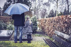 Father and daughter visiting grave. Widower and daughter standing at deceased mothers grave at graveyard. Mourning her death Royalty Free Stock Image