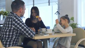 Father and daughter waiting for mother in cafe. Woman speaking with lovely smile. stock photos