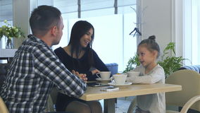 Father and daughter waiting for mother in cafe. Woman speaking with lovely smile. stock video
