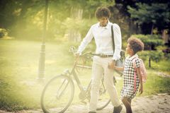 Father and daughter walking. African American father and his daughter walking trough park and talking royalty free stock photo