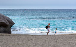 Father and daughter are walking along sandy beach of Adeje town on Tenerife island, Span Royalty Free Stock Photography